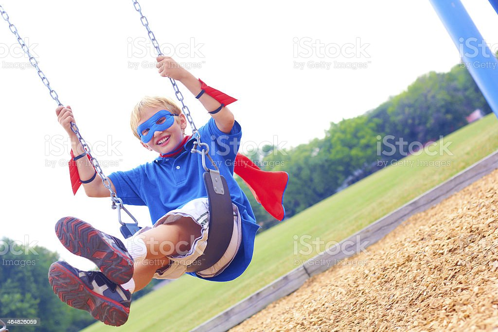 Superhero Kid Playing On Play Set stock photo