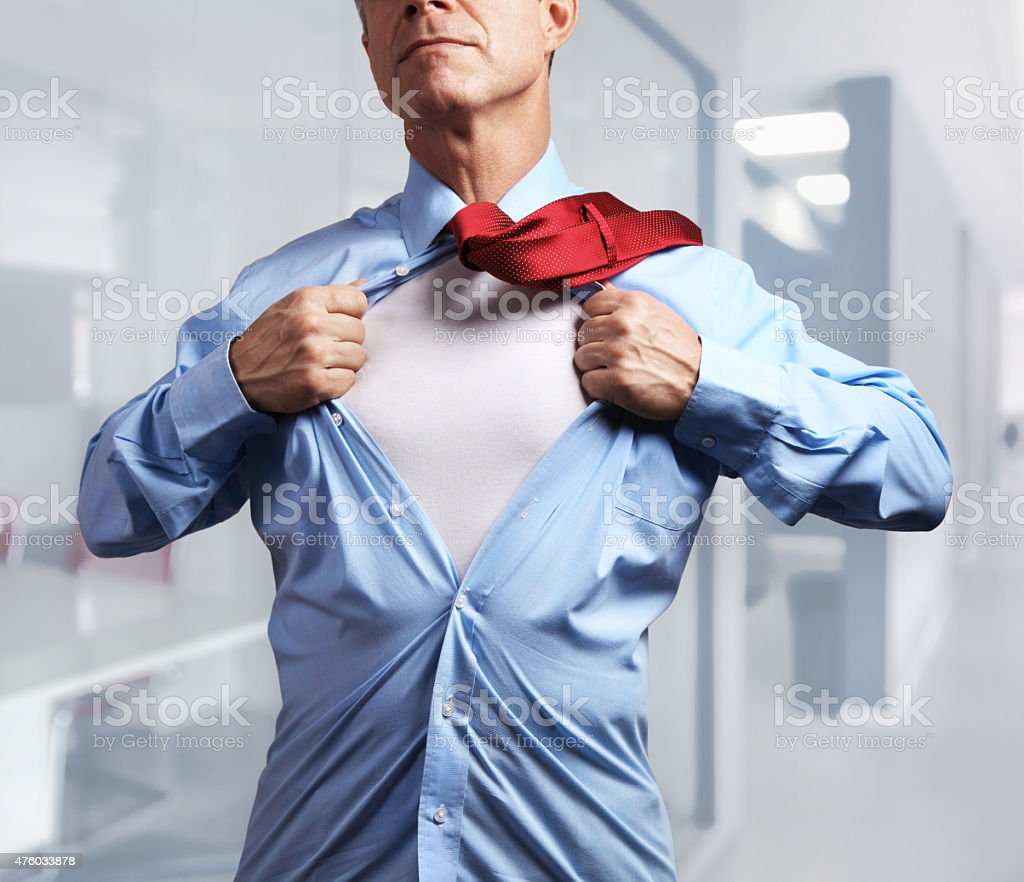 Superhero. Mature businessman tearing his shirt off over office background stock photo