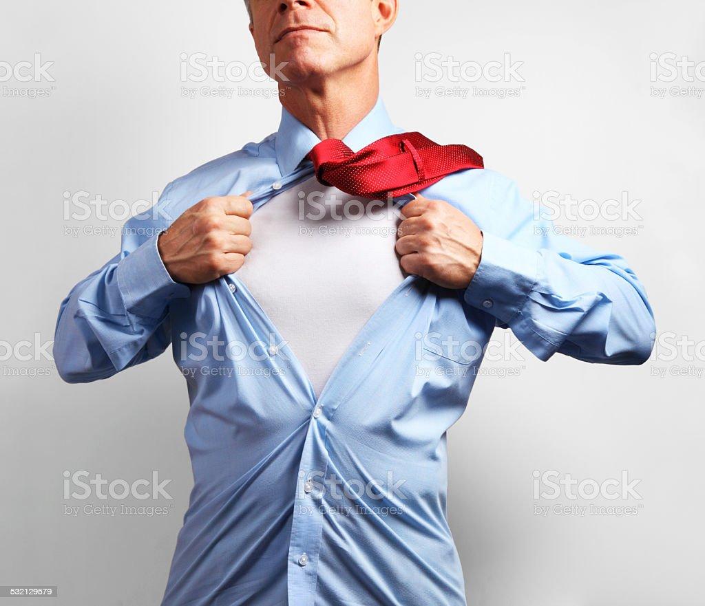 Superhero. Mature businessman tearing his shirt off over white background stock photo