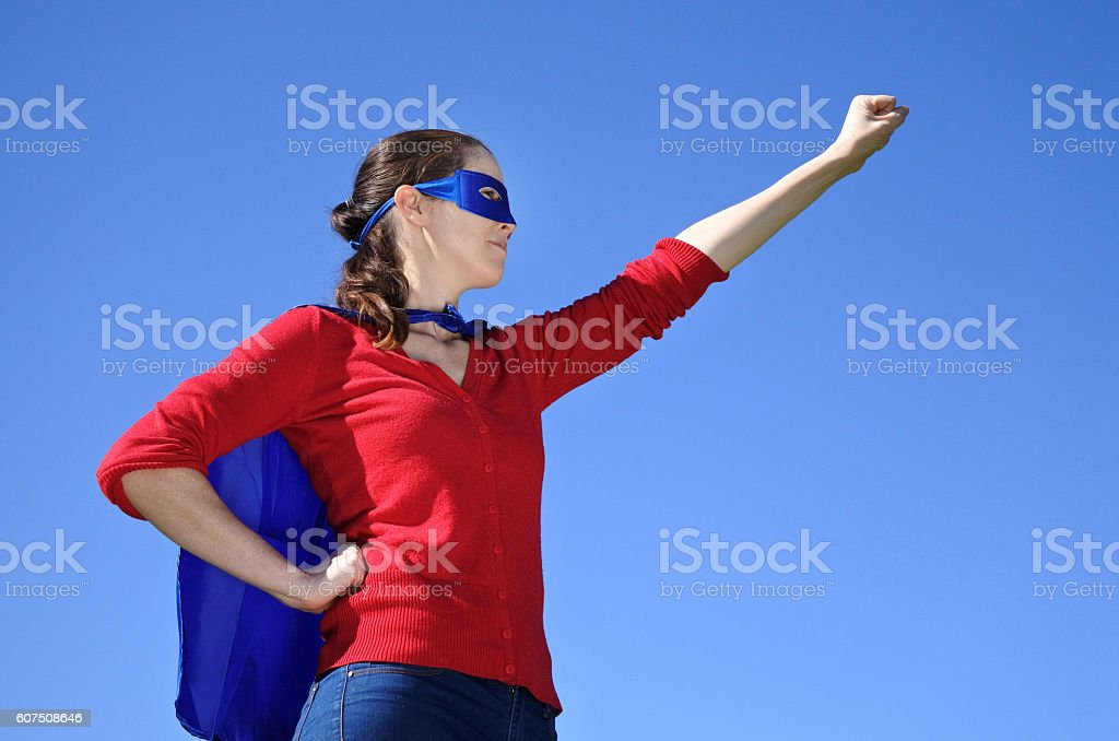 Superhero mother against blue sky background stock photo