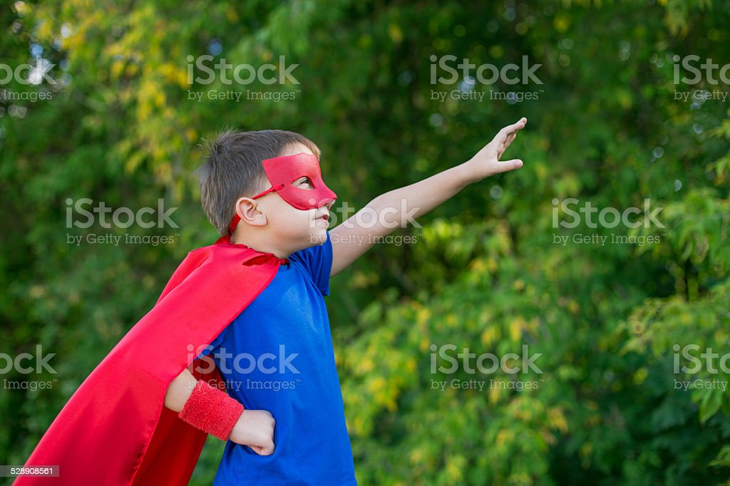 Superhero standing sideways and calling on forward stock photo