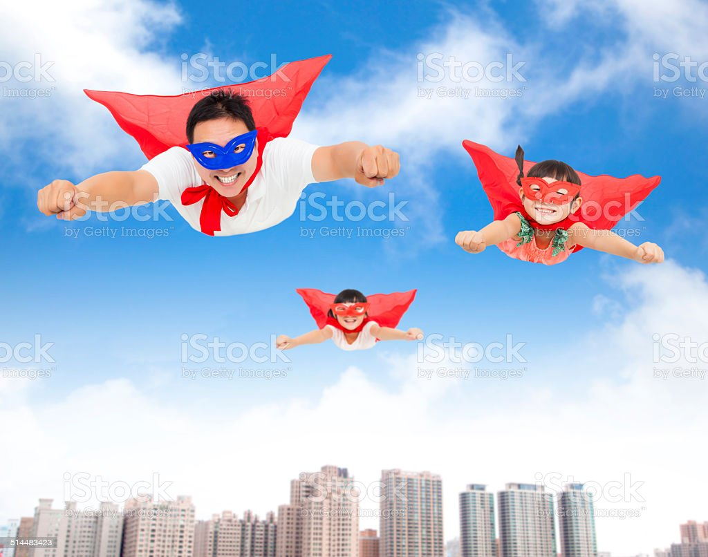superman and daughters  flying in the sky stock photo
