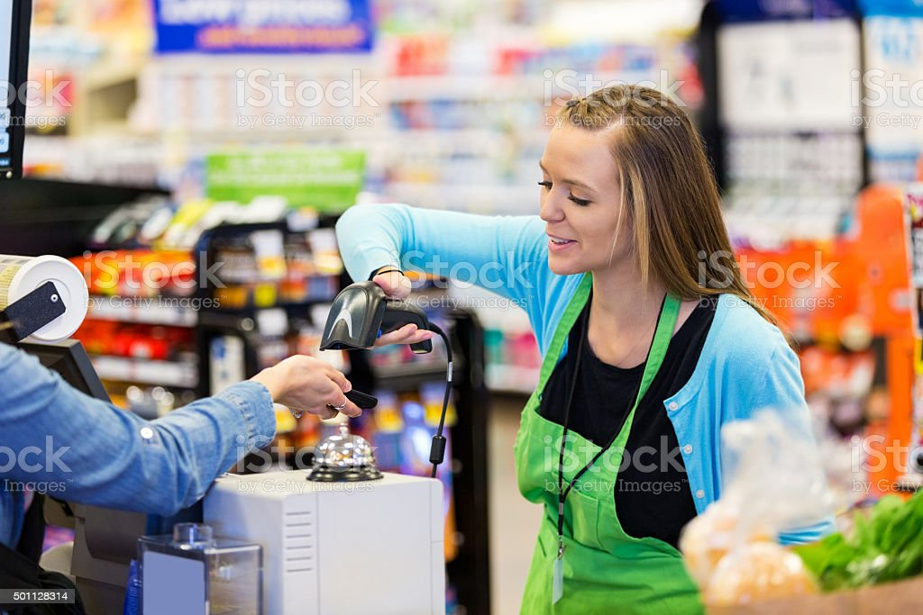 Supermarket cashier scanning smart phone to accept payment or coupons stock photo