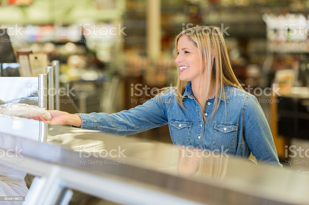 Supermarket customer buying meat from deli counter in supermarket stock photo