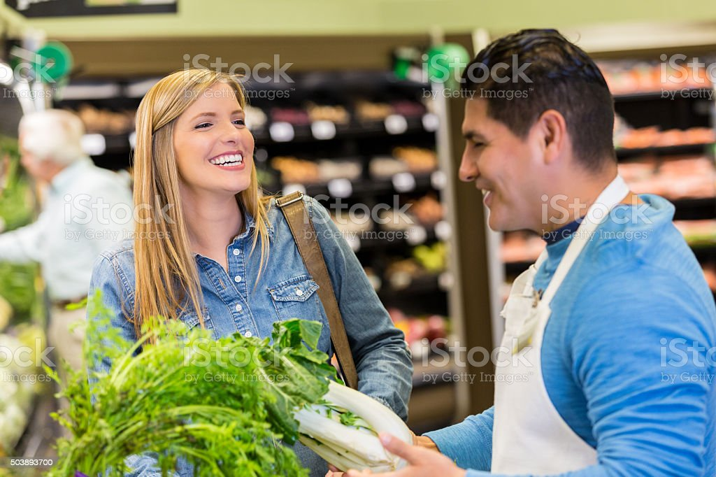 Supermarket customer talking to produce manager while shopping stock photo