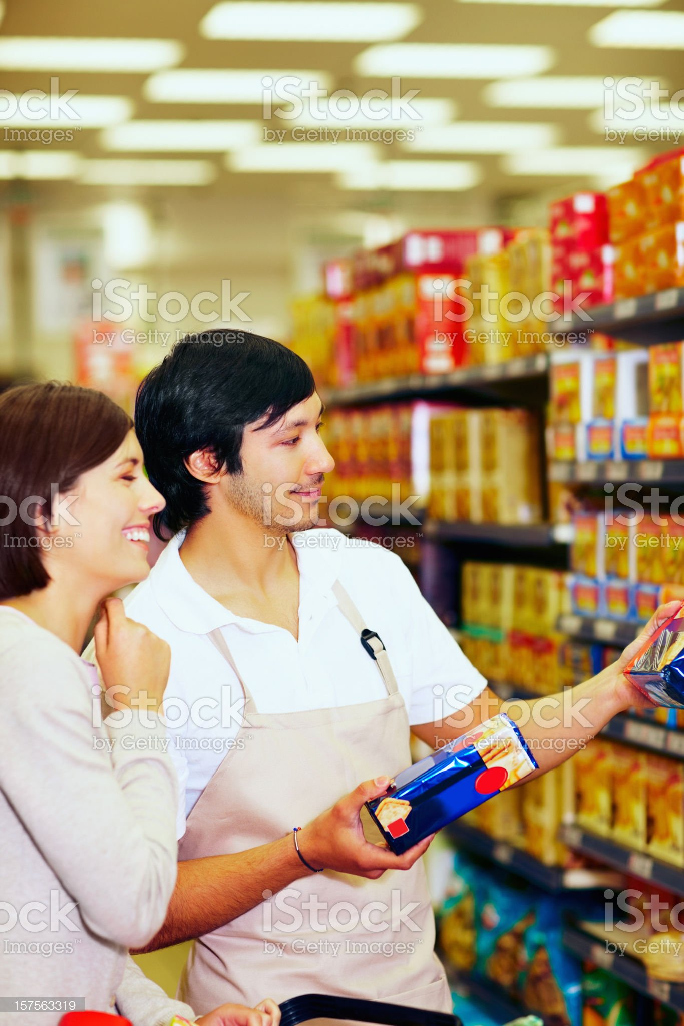 Supermarket employee assisting a customer with the products royalty-free stock photo