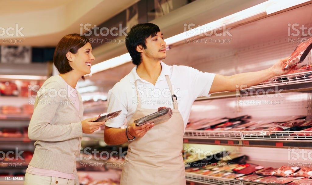 Supermarket employee helping a female pick packet of meat royalty-free stock photo