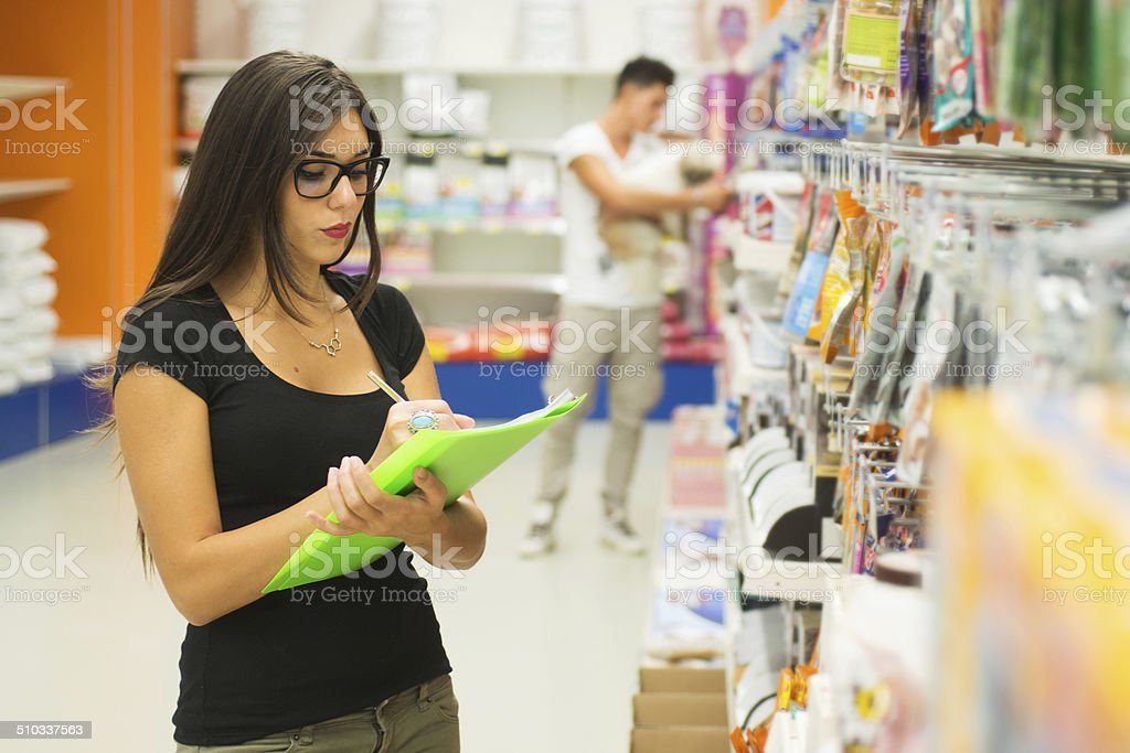 Supermarket Sales Clerk Checking Products. Customer with dog on Background stock photo