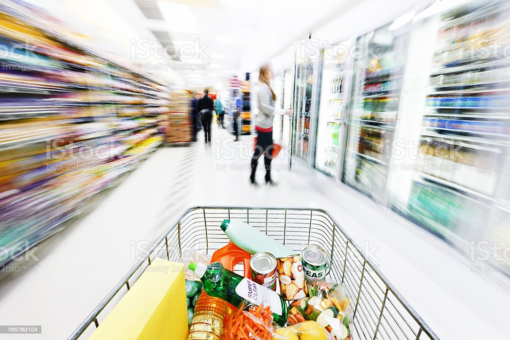 Supermarket shopping cart speeds down aisle, creating motion blur royalty-free stock photo