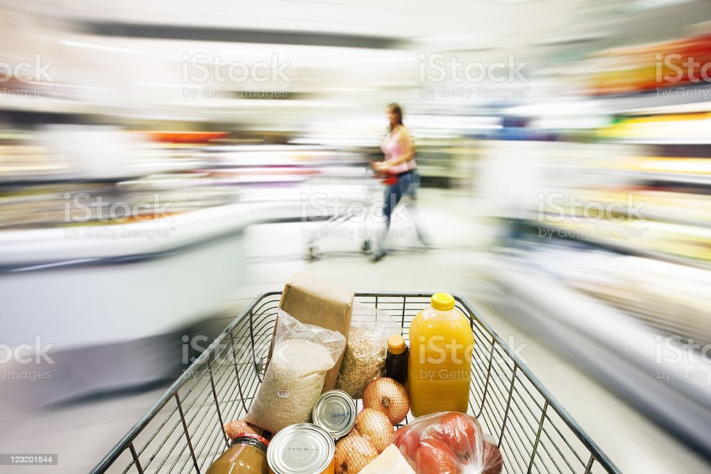 Supermarket trolley races through store with motion blur. stock photo
