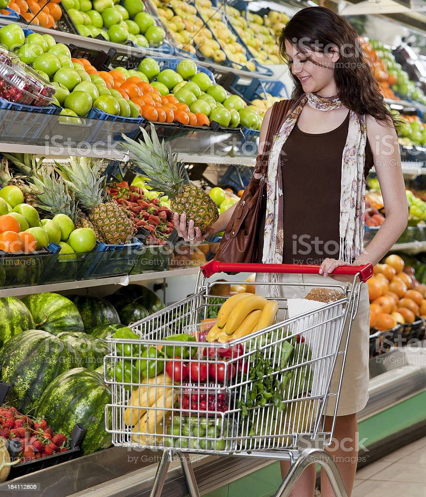 Supermarket - Woman choosing a pineapple royalty-free stock photo