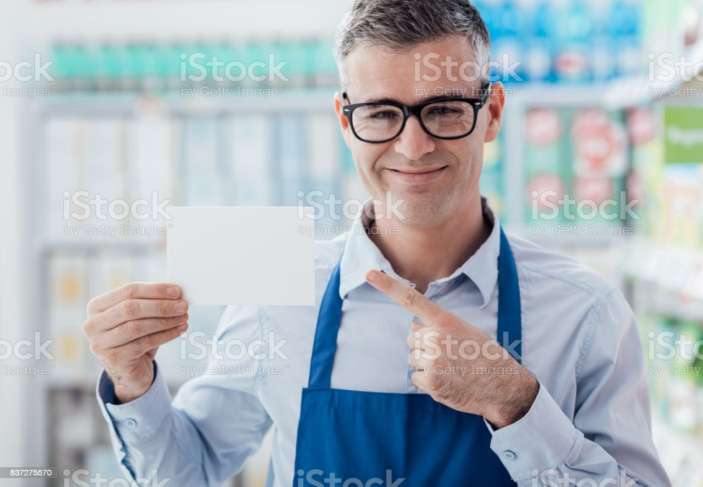 Supermarket worker holding a blank card stock photo