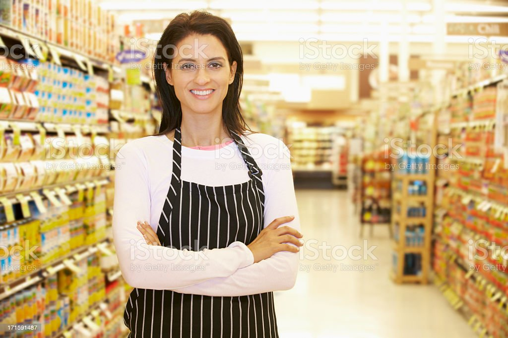 Supermarket Worker Standing In Grocery Aisle royalty-free stock photo