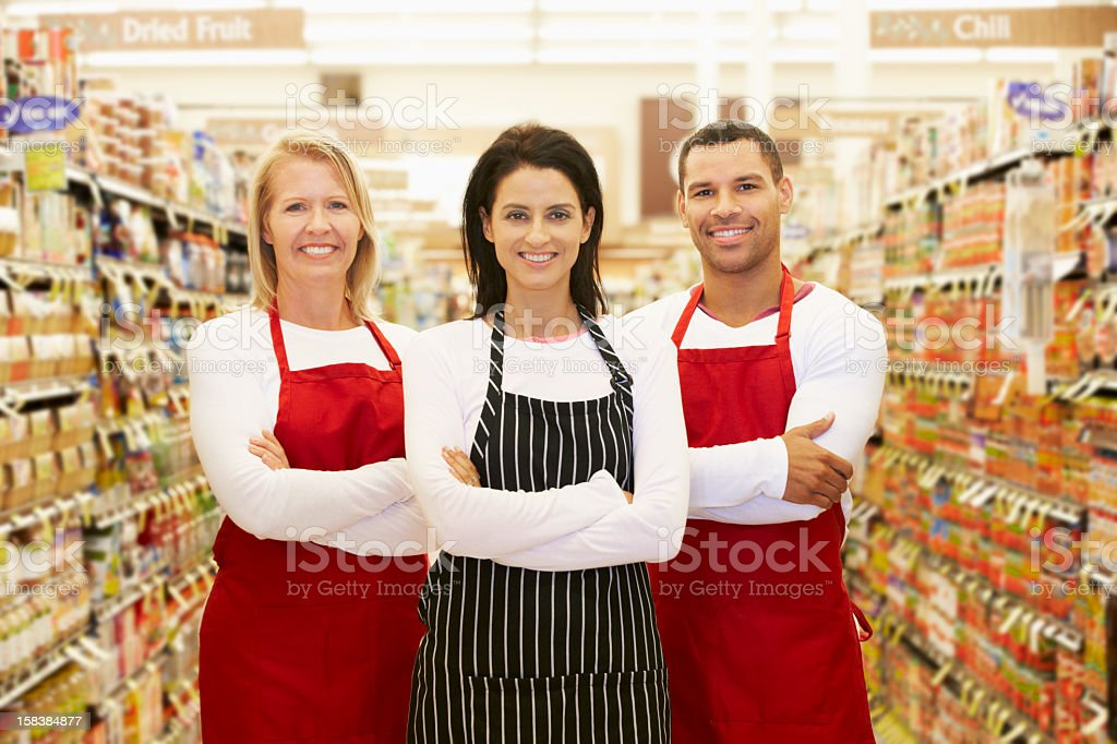 Supermarket Workers Standing In Grocery Aisle stock photo