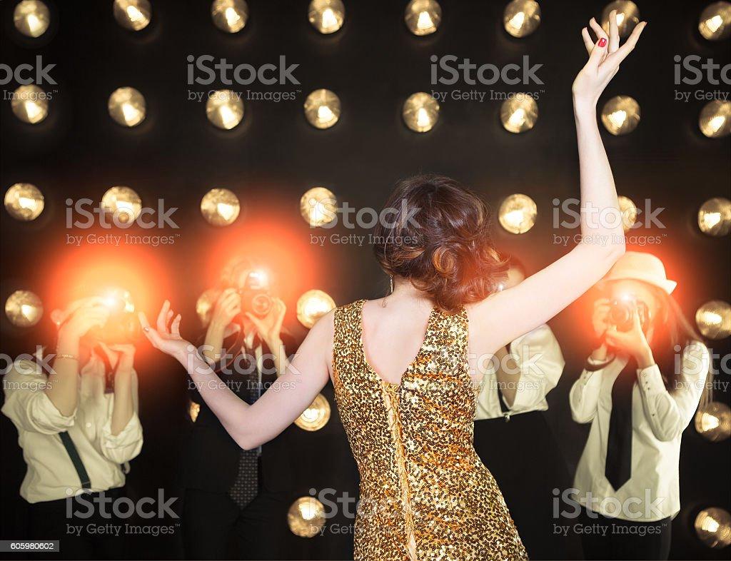 Superstar woman posing to paparazzi stock photo