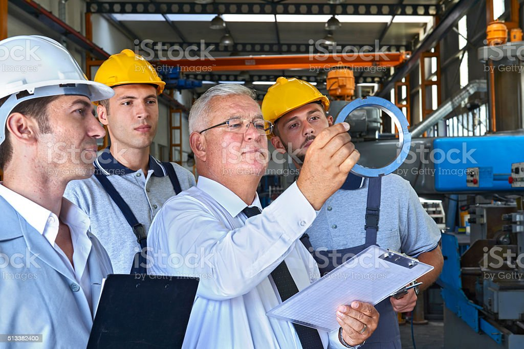 Supervisor and factory workers checking product stock photo