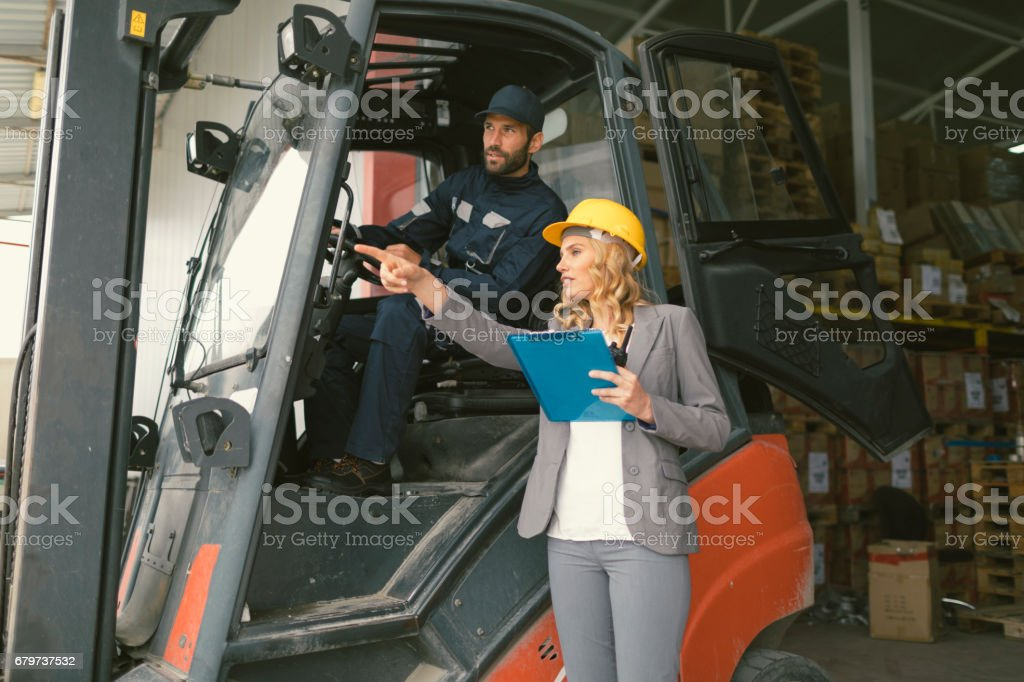 Supervisor and manual worker in warehouse stock photo
