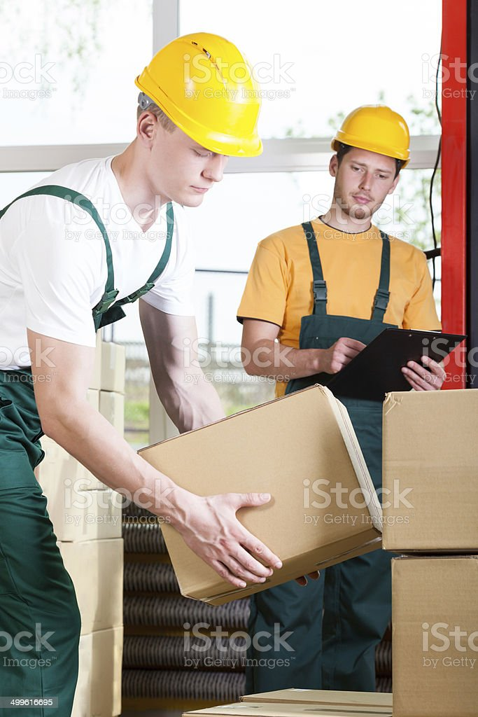 Supervisor and warehouse worker during job stock photo