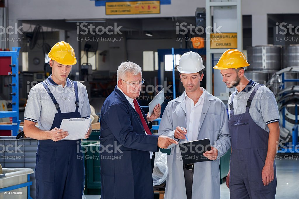 Supervisor and workers in factory stock photo