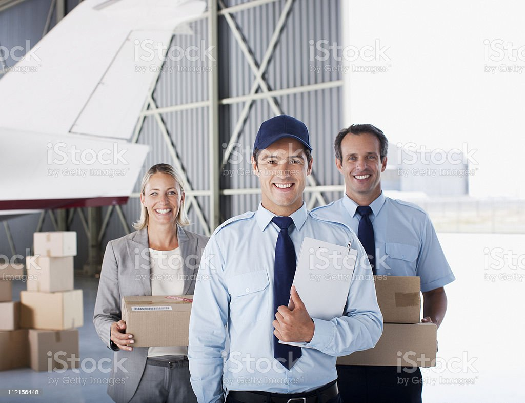 Supervisor and workers standing in hangar royalty-free stock photo