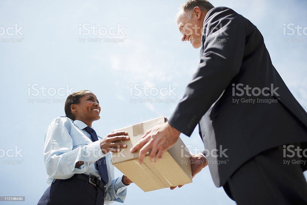 Supervisor handing box to worker royalty-free stock photo