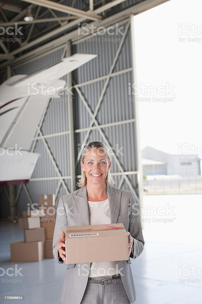 Supervisor holding box in hangar royalty-free stock photo