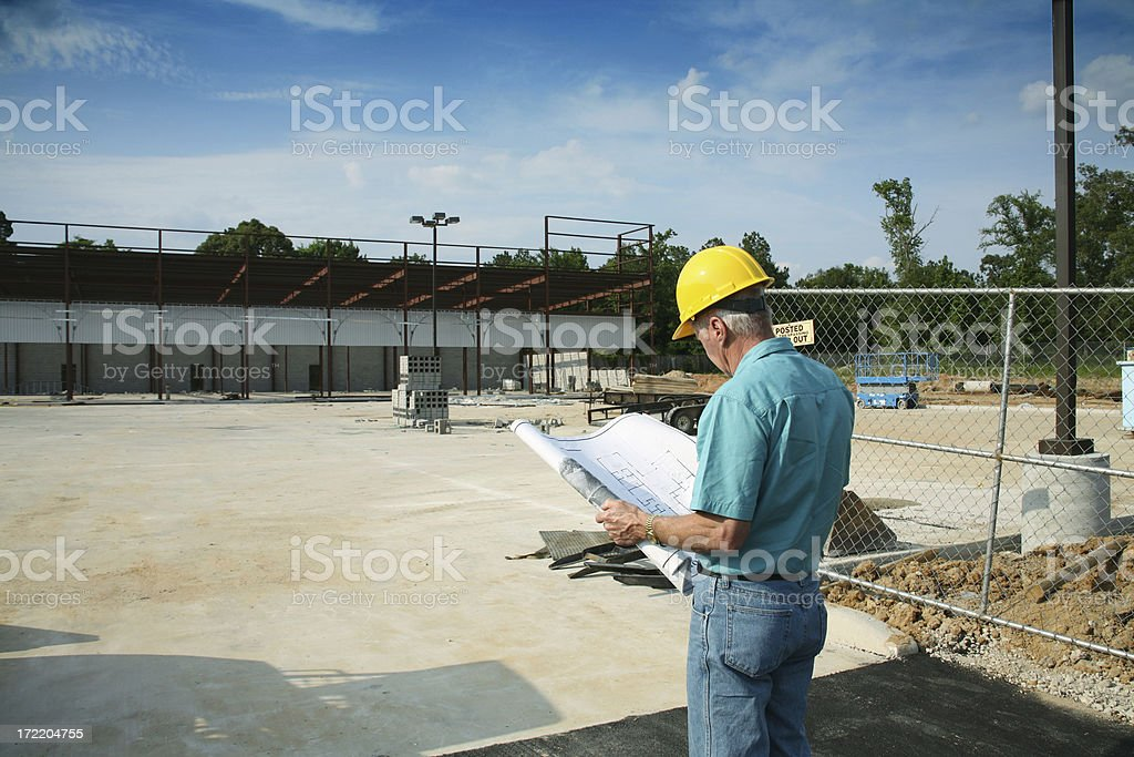 Supervisor man wearing hardhat and holding blueprints at construction site. royalty-free stock photo