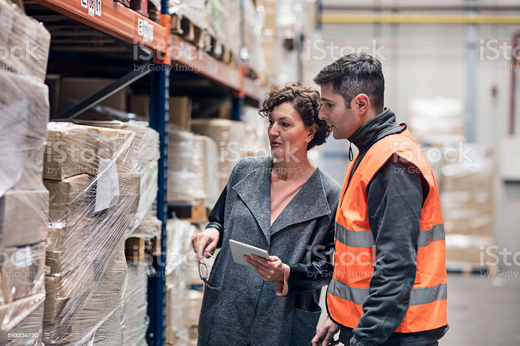 Supervisor talking with worker about the distribution products stock photo