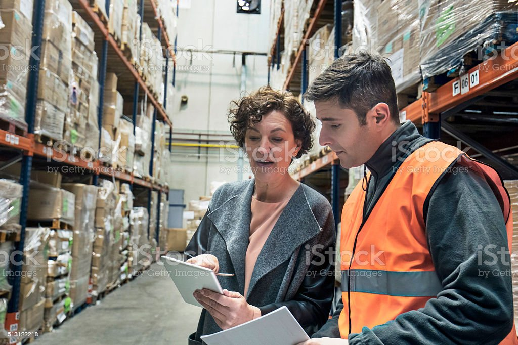 Supervisor talking with worker about the new products stock photo