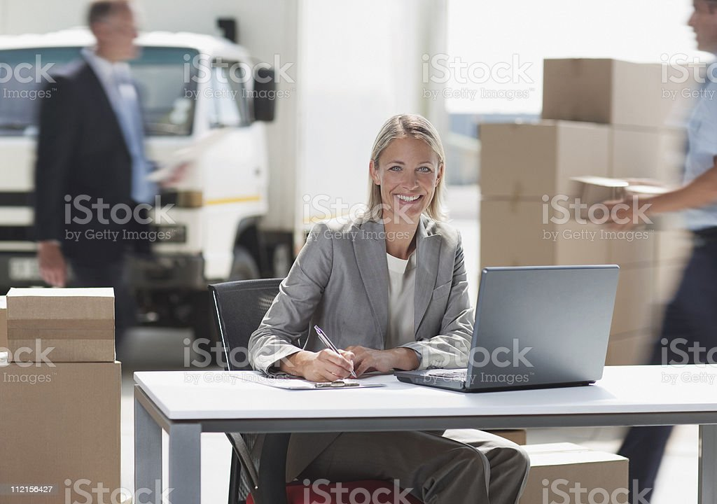 Supervisor working on laptop in shipping area royalty-free stock photo