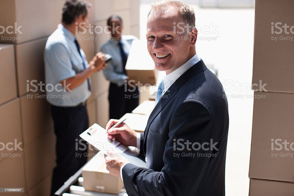 Supervisor writing on clipboard in shipping area stock photo