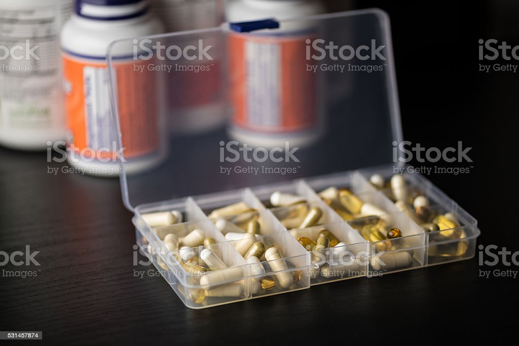 Supplements into daily pill box in front of bottles stock photo