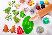 Supplies for preparing Christmas cookies decoration on a white table