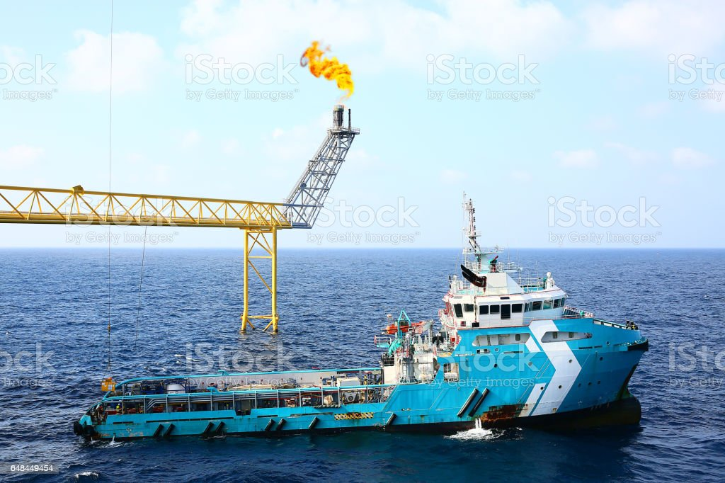 Supply boat transfer cargo to oil and gas industry and moving cargo from the boat to the platform, boat waiting transfer cargo and passenger between oil and gas platform for hard work in offshore. stock photo