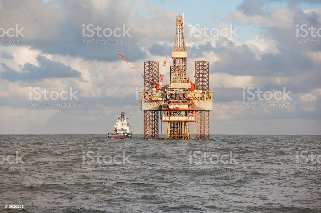 Supply ship and drilling rig stock photo