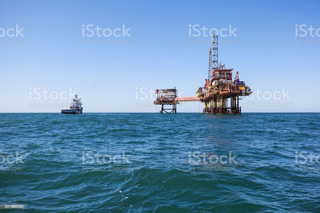 Supply ship aproaching oil platform stock photo