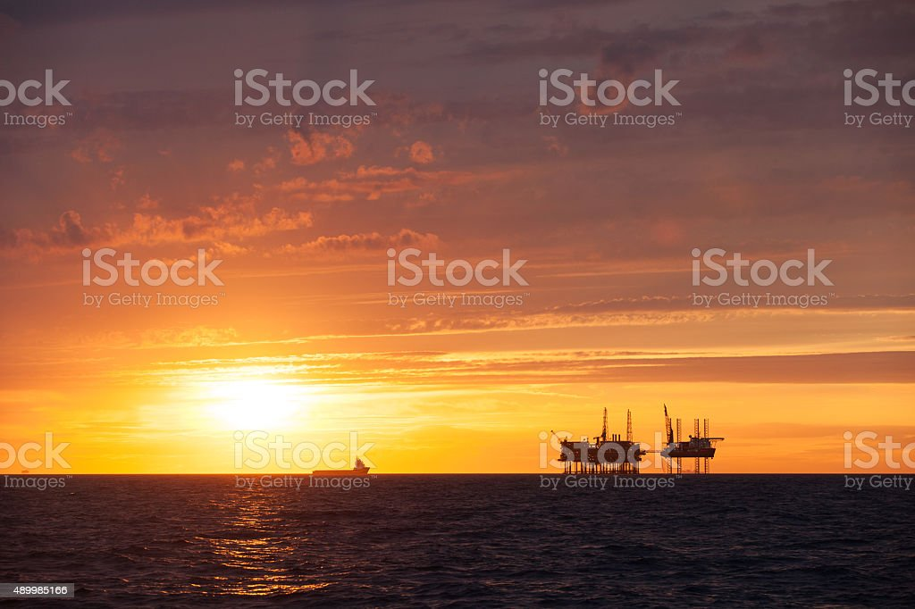 Supply vessel approaching oil platform during sunset stock photo