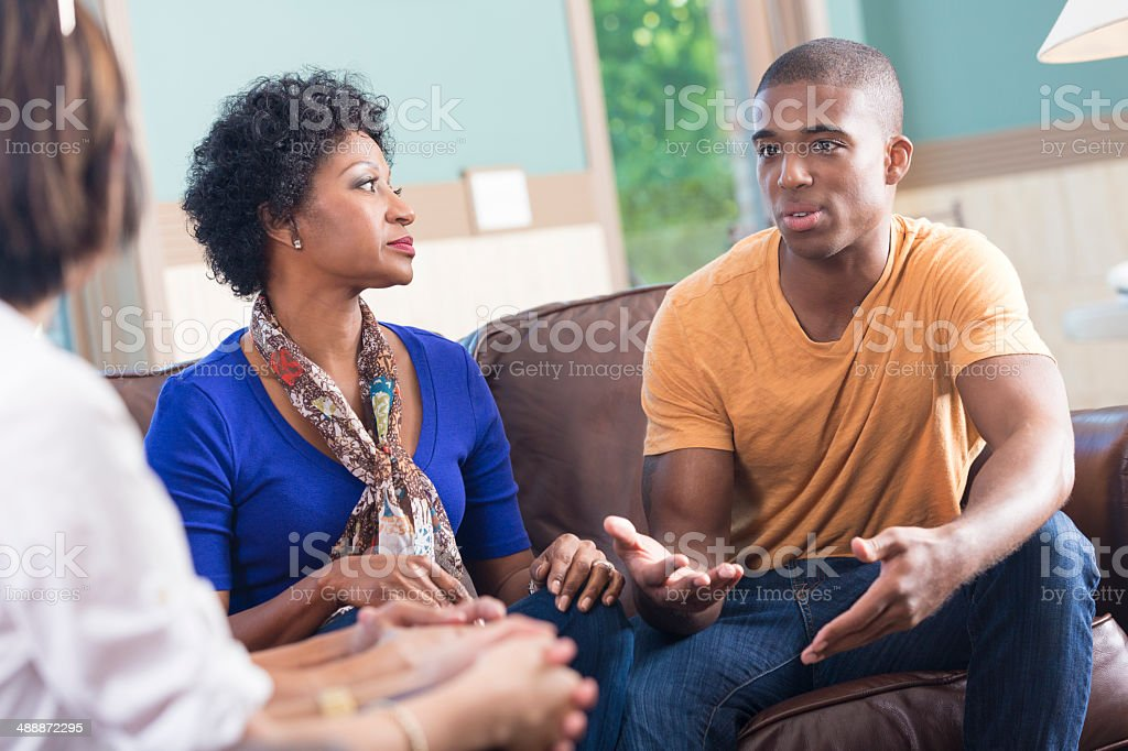 Support group listening to young man telling story during meeting stock photo
