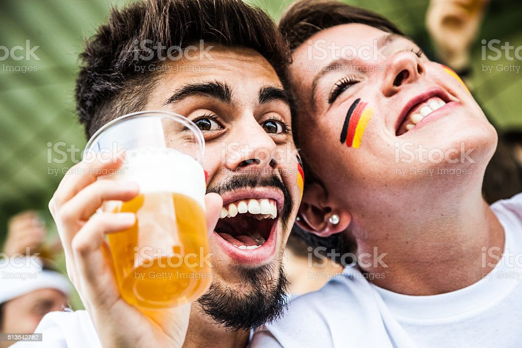 Supporters drinking beer at the stadium stock photo