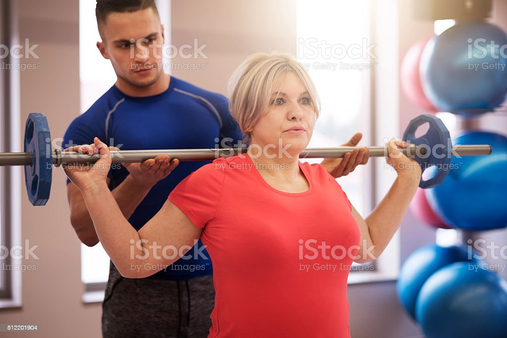 Supporting instructor exercising with mature woman stock photo