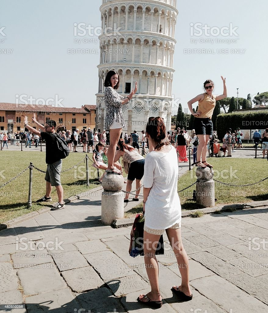 Supporting the leaning tower of Pisa - tourists enjoying themselves stock photo