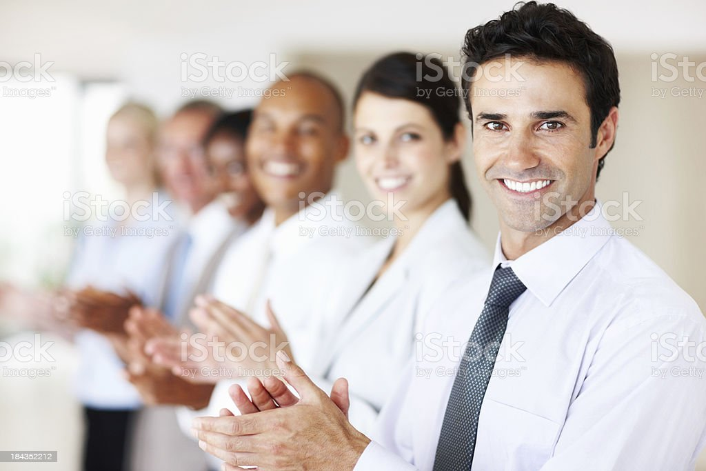 Supportive business man with colleagues applauding royalty-free stock photo