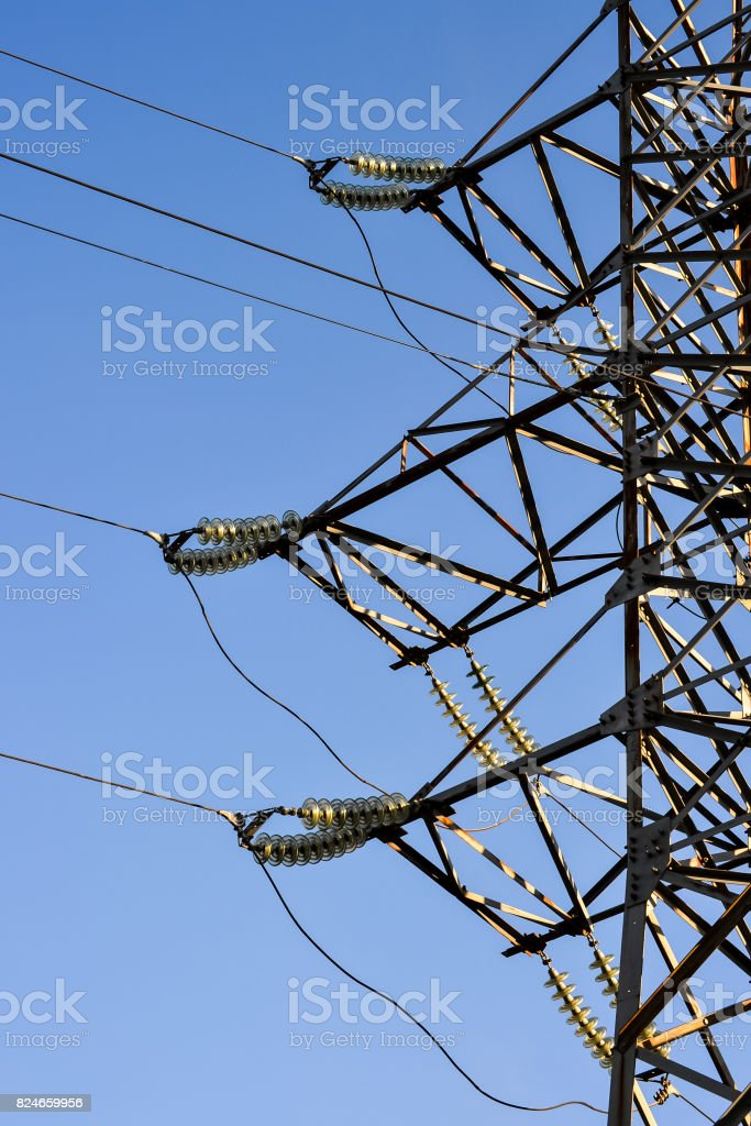 Supports high-voltage power lines against the blue sky. Electrical industry. stock photo