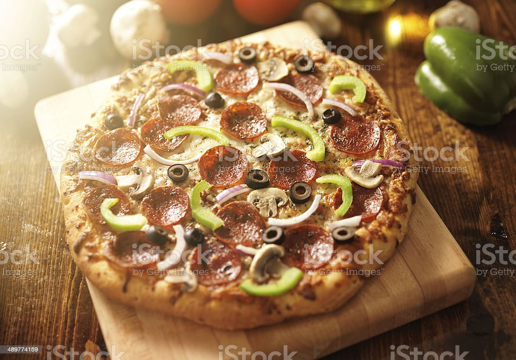 supreme italian pizza with pepperoni and toppings stock photo