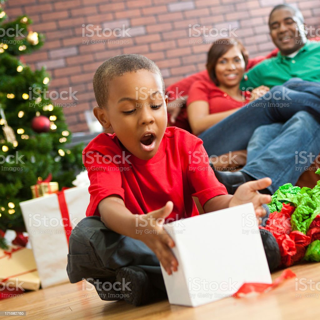 Suprised little boy opening present on Christmas morning royalty-free stock photo