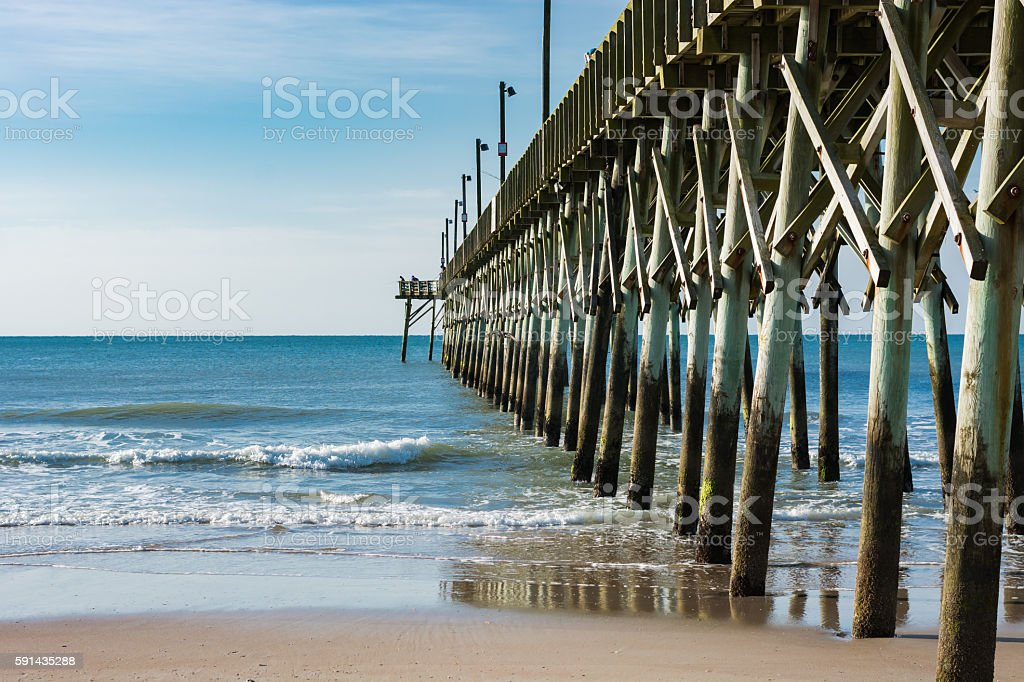 Surf City pier stretches into the ocean's horizon. stock photo