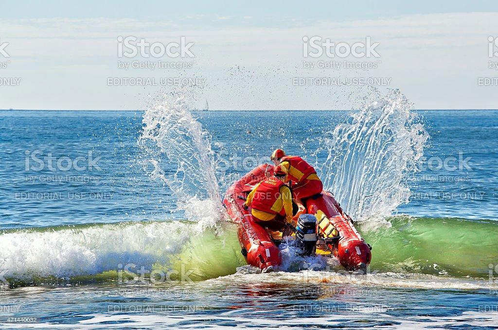 Surf lifesavers battle through the breakers stock photo