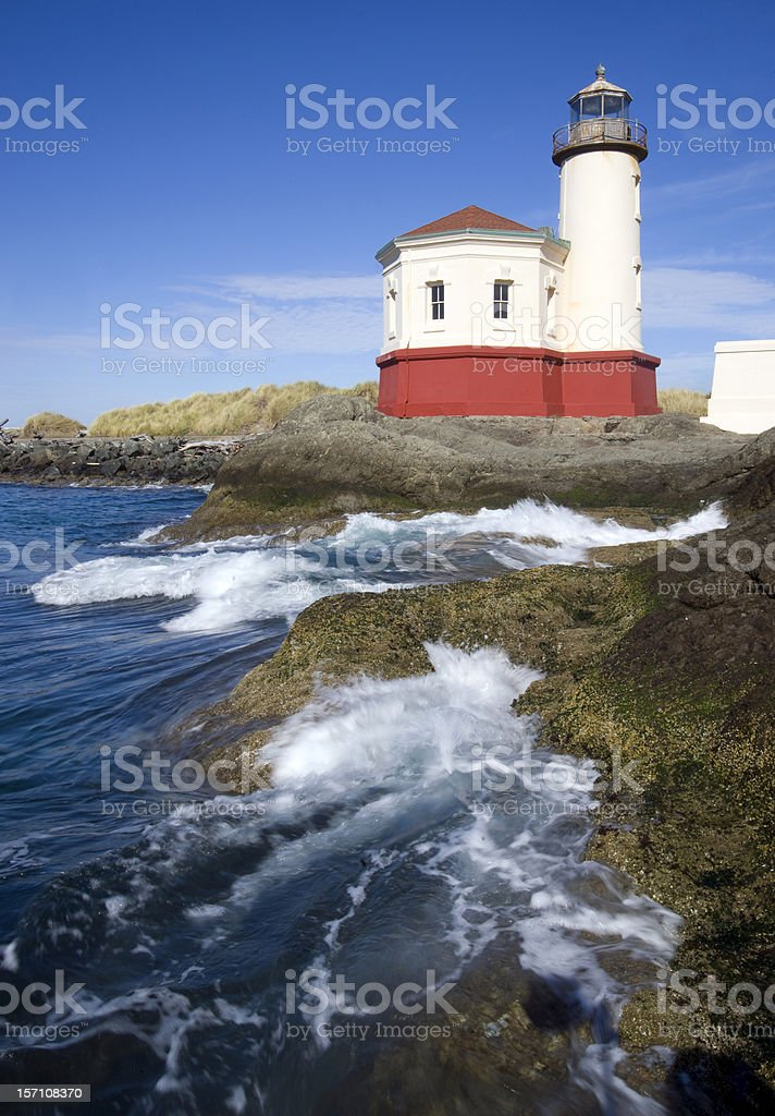 Surf Pushes over Rocks Coquille River Lighthouse Oregon USA stock photo