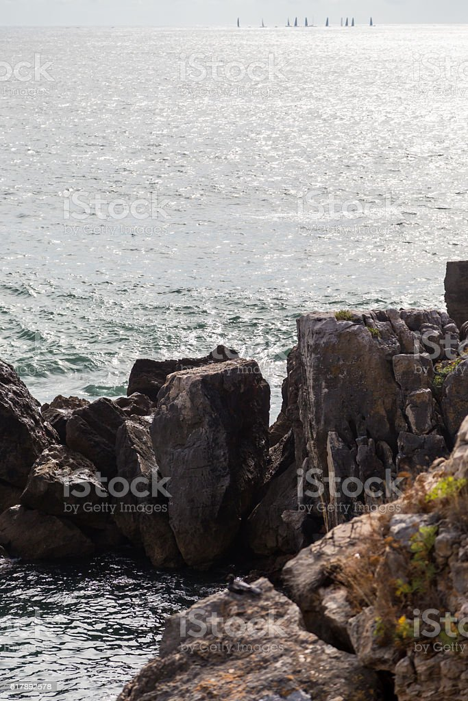 surf sea rocks with sails on horizone stock photo