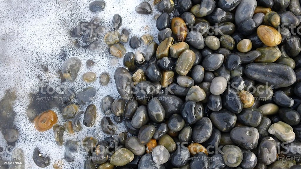 Surf washes over pebble beach stock photo